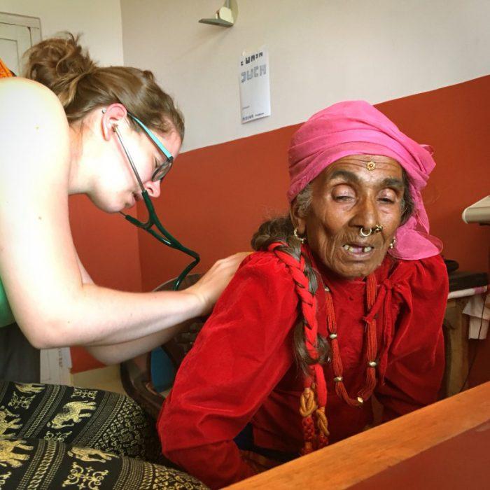 """Cathrin untersucht die Lunge einer Patientin. Ihr Blick ist fachmännisch korrekt angestrengt. Die Patientin übrigens hat es auch sichtlich schwer den Anweisungen:""""Tief, durch den offenen Mund ein- und ausatmen"""" zu folgen. Dies ist hier auch keine Seltenheit in Nepal. Die Menschen atmen insgesamt sehr ruhig, so dass man bei normaler Atmung eigentlich nichts während der Auskultation hören kann."""